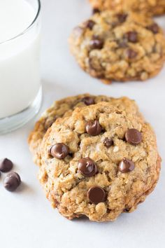 Two soft and chewy oatmeal chocolate chip cookies with a glass of milk.