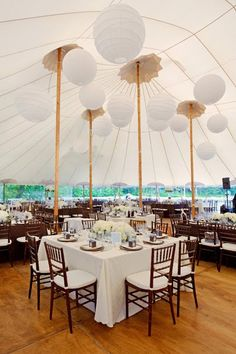 Sail cloth tent with fruitwood chairs, lanterns and ivory linens