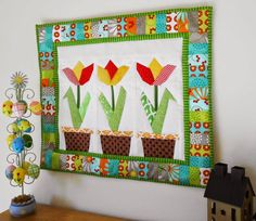 My Tulip Trilogy wall quilt.  A bright-and-breezy addition to my workroom - constructed almost entirely from scraps.  Check out my blog for a link through to the free pattern by Regina Grewe.