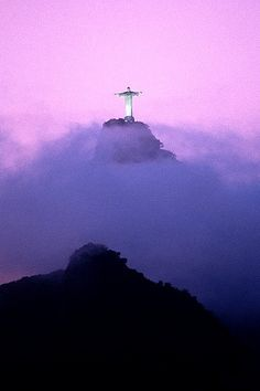 Christ the Redeemer, bathed in violet light, overlooking the city of Rio de Janeiro in Brazil.