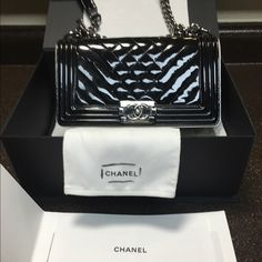 Chanel LE BOY metallic leather This beauty has been sitting in my closet in its box for over a year now. I've worn it 3 times maybe! It's in beautiful condition, comes with original box original Chanel tissue paper, authenticity card and also comes with original protective cloth like wrapping to protect this delicate piece. The purse itself has no wear on outside just a couple buffs on the inside which I'm including the original Chanel glove it came with to help polish metal parts. ️ price…