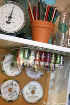 Organizing with Style: Great Tips from The Little Blue House like this idea from Vicki Chrisman for storing all her Stickles upside down on a old metal tray and how she hangs the digital CD's she uses most often on her bulletin board.