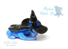 Wizard Dragon series.  This pretty sculpture of a sleeping dragon was inspired by the character of Rowena Ravenclaw. She has a deep blue body with black feathered wings, very detailed, a bright pink star-shaped rhinestone on her forehead, golden glitter on her eyelids, forearms and tail and a li...