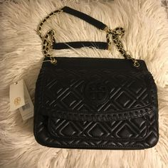 """Tory Burch Marion quilted shoulder bag Tory Burch Marion Quilted Shoulder Bag in black! * Flap front with magnetic snap closure. * Exterior pocket under front flap. * Interior zipper pocket and two open pockets. * Adjustable leather and chain shoulder strap with 18"""" (47 cm) drop when fully extended. * Height: 8"""" (21 cm) * Length: 10"""" (27 cm) * Depth: 3.5"""" (9cm) 100% authentic & NWT ships in dust bag  Still on TB website for full price! Tory Burch Bags Shoulder Bags"""