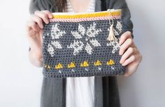 """Check out this """"knit look"""" crochet make-up bag by Mama in a Stitch! The fair isle pattern is created with tapestry crochet - get the pattern and make yours with Vanna's Choice (pictured in silver grey, linen, pink, and mustard) and a size I crochet hook."""
