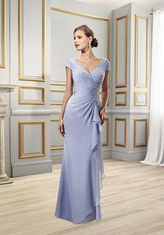 This ultra-feminine trumpet gown with a plunging v-neckline is inspired by Cinderella for a fairytale inspired wedding. Ruching at the asymmetric waist creates a figure flattering dress perfect for a mother of the bride. Finished with silver embroidery and a kick train, this floor length chiffon gown is truly awe inspiring.