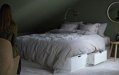 Sypialnia z białym łóżkiem z sześcioma miękko zamykającymi się szufladami, po trzy z każdej strony, idealnymi na dodatkowe poduszki i koce.
