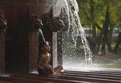 Un ragazzo si rinfresca seduto in una fontana