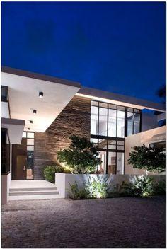 Fachada de casa iluminada con vidrio y piedra