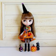This dress is perfect for your Neo Blythe doll to wear to a Halloween party! It's made of bright orange fabric with pumpkins, ghosts, witches, and other spooky characters and has a bit of glitter in t