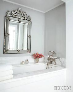 a Venetian-style mirror adds elegance to a white bathroom