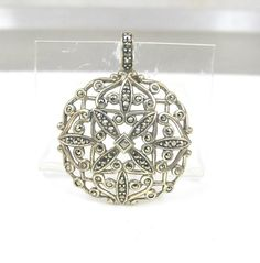 Beautifully detailed vintage Sterling Silver pendant slide enhancer with open scroll work lacy design with brilliant diamond like sparkling marcasites. Pendant has a timeless elegant look that works well worn on a chain or thick Sterling collar or long black ribbon. The bale is large enough to accommodate a thick chain. Either way, this will make the perfect piece to add a bit of sparkle to any outfit! In excellent condition with all stones present and secure. Pendant slide is hallmarked…