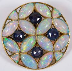 Fine 1920's opal and blue sapphire circular pendant / brooch, the circular panel set with four blue sapphires within an open lattice work design of marquise shape opals in yellow metal setting, 30mm diameter.
