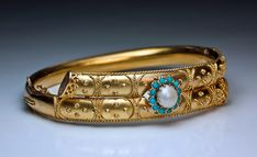 An Antique Etruscan Revival Crossover Bangle Bracelet, St. Petersburg, circa 1885. A Victorian era 14K yellow gold bracelet with applied gold beads and twisted threads (filigree) in ancient Etruscan style is centered with a prong-set half pearl within a cabochon turquoise surrounding.