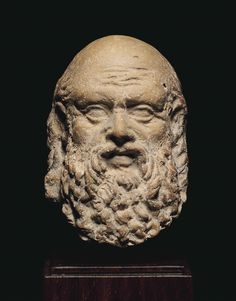A GREEK TERRACOTTA HEAD OF A MAN. HELLENISTIC PERIOD, CIRCA 4TH-3RD CENTURY B.C. Perhaps a philosopher, depicted with a bald pate, his thick hair arranged in corkscrew curls descending low around his head, his face with a knitted brow, articulated eyes, and a full beard and mustache. 2 ¼ in. (5.8 cm.) high. I Christie's
