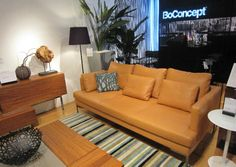 Love everything here: Contemporary furnishings. BoConcept sofa (light, carmel colored modern sofa with sleek metal legs); sculpture on the side table, striped rug, metal bowl etc etc