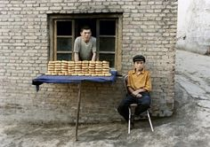 Photo © Stacey Irvin. Image title: Waiting for Change. Caption: During my first trip to Kashgar I bought a bagel-like bread called girde nan from two handsome young men along a quiet lane. I photographed the bakers as I waited for their younger brother to fetch change for my purchase. On my next visit in 2004, I brought this photograph to give to them. Unfortunately, their bread stand was vacant. An American man, who lives in Kashgar and speaks fluent Uighur, offered to help me search for…