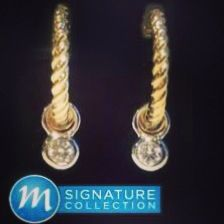 Two time earrings from Markmans Signature Collection. 14k gold with bezel set diamonds weighing .18 carats.
