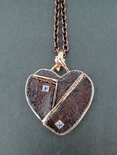 """A 2016 """"Unbreakable Heart"""", """"Picasso Heart from the Rose Period"""", made of 18k rose gold, sterling silver and rusted iron with two bezel-set 2.5mm square sapphires on a brown stainless steel chain with 18k rose gold clasp and catch. Designed and made by llyn strong."""