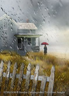 Trevillion Images - man-with-umbrella-near-seaside-cottage