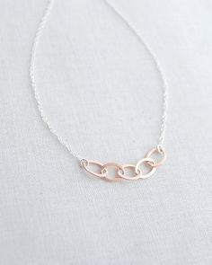 Rose Gold Five Ring Necklace by Olive Yew. Five linked rose gold ovals hang beautifully from shiny silver chain.