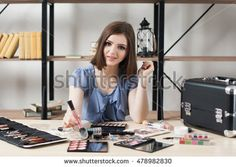 Pretty smiling make-up artist at workplace. Female visagiste looking at camera while she using rouge with brush. Fashion, makeup, beauty concept
