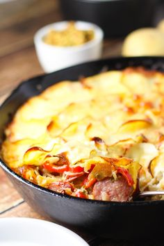 This Sausage and Sauerkraut Skillet Bake, inspired by Oktoberfest, combines two favorites of polska kielbasa sausage and sauerkraut. It's topped with emmentaler cheese and thin potato slices and baked until bubbly. | platignsandpairings.com