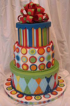 About a Boy - This is the novelty tiered cake I ented in the Capital Confectioners That Takes the Cake  show in Austin.  The patterns and colors were inspired by a series of scrapbook paper.  The box tops and loop bow were done in gumpaste.  The cake decorations were done in fondant.  The argyle stiching was piped with royal icing.  I placed second.