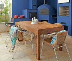 Com forno à lenha e churrasqueira, a varanda da cobertura ficou mais vibrante com o tom de azul intenso. A mesa é de madeira de demolição. Criação da arquiteta Andrea Murao