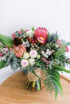 Pretty protea bouquet: Photography: Kibogo Photography - kibogophotography.com Read More on SMP: http://www.stylemepretty.com/australia-weddings/2016/07/19/australian-malaysian-cultural-garden-wedding/