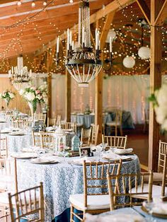 Whether they're modern wrought-iron chandeliers, antique crystal ones or chandeliers wrapped in greenery, ballroom-appropriate lights hung over a few dinner tables will transform your wedding reception into an elegant ambiance.