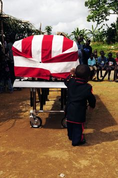 A.J.Tarwoe, the son of U.S. Marine LCpl Abraham Tarwoe, 25, of Providence, R.I. stands guard over his father's casket.