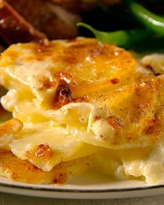Potatoes Dauphinoise       1 tablespoon unsalted butter, room temperature  2 1/2 pounds Yukon Gold potatoes  2 1/2 cups heavy cream  1 1/2 cups whole milk  1 garlic clove, smashed  1 teaspoon coarse salt  1/4 teaspoon ground white pepper  4 ounces Gruyere cheese  1/8 teaspoon freshly grated nutmeg