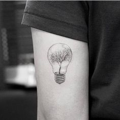 Surrealist tree light bulb tattoo on the back of the left arm, for her grandfather.