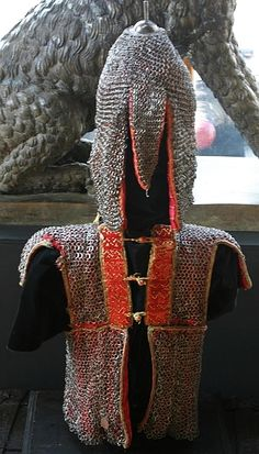 Indian armor for a boy, 18th to 19 century, riveted mail zirah kulah/kulah zirah (mail helmet/hood) with a plume holder, and zirah (mail shirt), both with red silk lining, the mail shirt opening at the front and secured by three silk loops on rectangular panels of padded red silk enriched with brass nails, extending over the shoulders, the neck fitted with an early padded green silk panel also studded with brass nails.