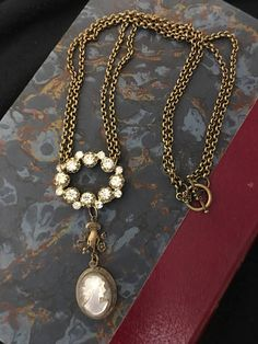 Dixie is a vintage assemblage necklace that features an antique European cameo, marked 800 (sterling). A Victorian reproduction hand connector leads to an antique rhinestone oval brooch that has been altered. Antiqued rolo chain in a double strand lead to to the antiqued bronze