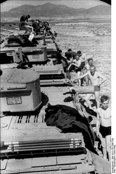 A line of Panzer 3 tanks with their crews at rest