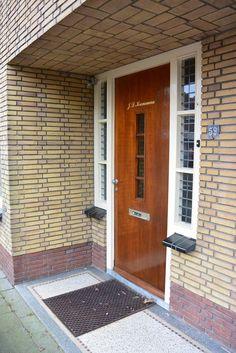 Jaren30woningen.nl | Mooie overdekte entree naar een jaren '30 woning met terrazzovloer, kenmerkende voordeur met zijlichten met glas in lood