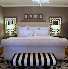 Classic bedroom: mirrors behind lamps, tufted headboard and black and white bench adds some tang