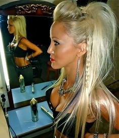 Long platinum blonde with braids on the sides, bumped bangs in a lightly teased half-updo hairstyle.