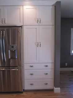 fridge by back door surrounded by cabinets?