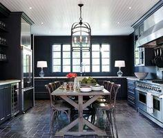 Lovely kitchen sports dark gray walls, symmetrical styling, and farmhouse table. #interiordesign #homedecor