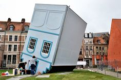 Employees stand in front of an installation entitled 'The House Fallen Down From the Sky' by French artist Jean-François Fourtou displayed as part of the 'Lille Fantastic' festival and the Lille3000, a cultural program promoted by the city, in Lille, northern France. (AFP)
