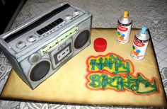 "80's Boombox - For a client's 80's themed 30th Birthday party. 3D boombox on top of a sheet of fondant ""carboard"" for break dancing, Krylon cans (RKT) used to ""spray"" Happy Birthday! Again....I think another cake of mine that won't be getting cut by it's recipient!!"