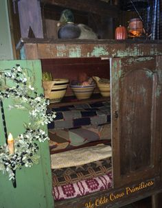 Antique pie safe decorated with old benches a lantern coverlets crazy quilts and some antique yellow ware bowls Ye Olde Crow Primitives