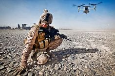 U.S. Marine Corps Cpl. William Cox shields himself from flying rocks and sand as an MV-22 Osprey aircraft prepares to take off in Nimroz province, Afghanistan, on Dec. 30, 2011.