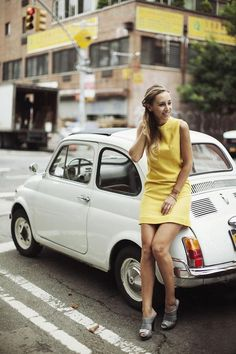 Girl in yellow dress posing with her vintage FIAT 500