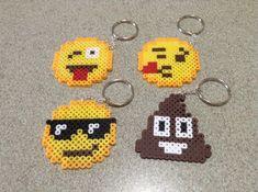 vier Schlüsselanhänger mit Emoji Gesichter aus Steckperlen, jedes hat eine verschiedene Miene