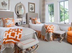 A bold color unifies a mix of patterns in this room. The Chinoiserie accent pillows, striped dust ruffles and geometric patterned throws all boast the same vibrant orange