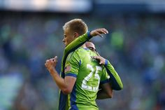 Mauro Rosales, background, congratulates teammate Andy Rose after Rose scored against the Vancouver Whitecaps in the first half. Photo by John Lok / The Seattle Times